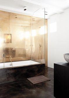 petite salle de bains en blanc et marron foncé avec une baignoire douche et panneau mural couleur laiton