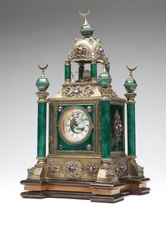 A Continental silver-gilt & enamel mantle clock, 19th century, marked '925', apparently unsigned, made for the Turkish market, the circular dial with Turkish numerals centering a painted landscape scene, within a temple-form case with crescent moon finials atop the dome and four corner columns, decorated overall with pierced scrollwork and set with amethysts, seed pearls and white onyx, on an associated later wooden base.