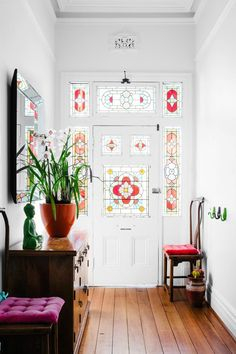 White hallway with colourful stained glass front door.