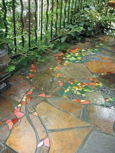 A whimsical grapevine, with colorful tile leaves and cullet glass clusters of grapes, on a stone porch built by Jim DuBois: