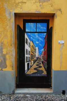 Opening Doors With Art In Madeira, Portugal - by Olivia Katrandjian @okatrandjian, @HuffingtonPost | These are some of the many scenes and words painted onto the deteriorating doors of Santa Maria Street in Funchal, the capital of the Portuguese island of Madeira. Two years ago, José Maria Montero had an idea -- to have artists paint the deteriorating doors of abandoned shops and homes. He asked over 100 artists, most of them island natives, to participate in the Arte Portas Abertas…