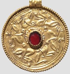 An Anglo-Saxon gold pendant,  6th/7th century. Round pendant with fine animal decoration, centrally one almandine in a bezel, twisted rim with carrying loop.