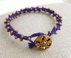 This purple bracelet is a Kumihimo round braid. Kumihimo is a Japanese braiding technique. I've been admiring the technique for some time now. I finally got a chance to use my Kumihimo loom disc and I love it! I think I might be hooked. The name Shiran is a type of Japanese orchid. I really enjoyed making this. The button is just phenomenal! A vintage brass filigree button with a mirrored back. It's kinda tough to see in the picture, but it's got a shiny, reflective backing that can be seen…