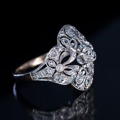 Antique Edwardian Bow Motif Diamond Engagement Ring, Edwardian / early Art Deco, circa 1910. An antique platinum-topped 18K gold openwork milgrain ring is centered with a sparkling old European cut diamond flanked by two bows and lace-like designs embellished with old mine and old rose cut diamonds.