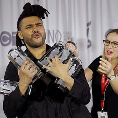 #JUNOS Toronto-born artist The Weeknd struggles to hold the multiple Juno Awards he won while posing backstage at the awards ceremony in Calgary. |  Chris Boli/Reuters