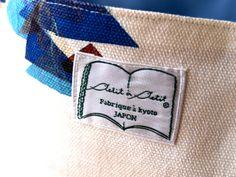 写真は、プティ・タ・プティのオリジナルタグです。本の立体感を出すために、左右別の織り方になってります。この小さなタグに3種類の織り方を入れています。「こんなこと頼まれるのは初めてやわ!」と織ネーム屋さんに驚かれました。(ウエストピローには他の小さいタグがついてます)実はナカムラの実家は京都、西陣のネクタイメーカーだったので、小学生の頃からいろんなブランドの織ネームをカットしたり折ったりを手伝っておりました。そんなわけで、ひとかたならぬ思い入れのある織ネームのはなしでした!