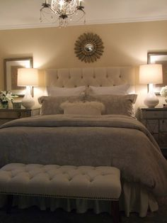 Mirrored side tables, sunburst above bed, pictures behind table lamps