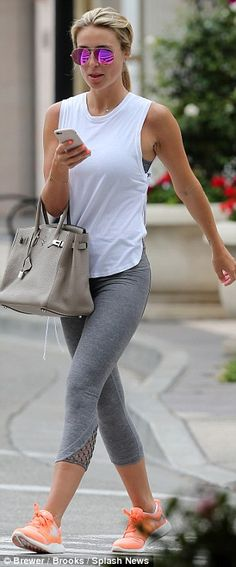 Another day, another outfit: Showing off her huge range of workout fear, she opted for a pair of grey leggings with a white vest top and orange trainers