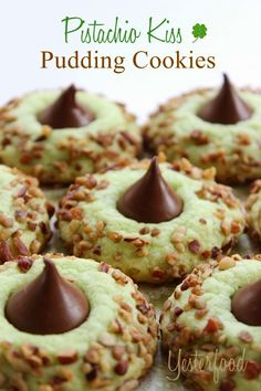 PISTACHIO KISS PUDDING COOKIES  (Makes about 36 cookies) ==  1 pouch (1 lb 1.5 oz.) sugar cookie mix, 1 box ( 3.4 oz.) pistachio instant pudding mix, 2 T flour, 1/2 c unsalted butter melted and cooled, 2 large eggs, 2 drops green food coloring (optional), chopped nuts, 36 unwrapped chocolate kisses  =======