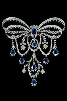 Chaumet 'Garland Style' Stomacher. Platinum & gold bowknot stomacher brooch, the ribbons in two loops each divided into a line of diamonds edged w/sparks, & lines of stylised laurel meeting at a center octagonal sapphire surmounted by 3 pear-shaped diamonds, & w/laurel leaves terminating in 3 pear-shaped diamonds on each side of the festoon below, & terminating in a laurel wreath w/one sapphire w/in & another at the base, & 2 pear-shaped diamond drops to each side