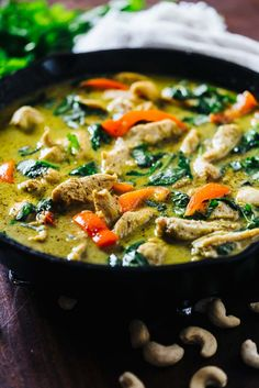 Chicken curry made with coconut milk with spinach and peppers in a cast iron skillet
