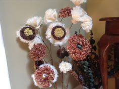 Large, layered, fabric flowers with button centers on rustic barbed wire.