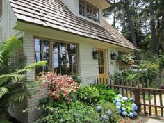 Wonderful entrance to cottage for sale in Carmel with black lantern lights, wooden fence and colorful yellow door