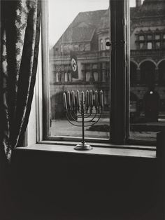 A Jewish menorah defies the Nazi swastika, 1931. It was the eighth night of Chanukah in Kiel, Germany, a small town with a Jewish population of 500.