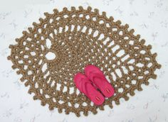 """This is a large handmade jute throw rug, in a pineapple pattern. Its unusual design makes it a perfect accent rug. It's crocheted with a double thickness of all natural jute twine, and is perfect for those places where you want that touch of the primitive. It measures about 45"""" x 33"""" at the longest and widest points."""