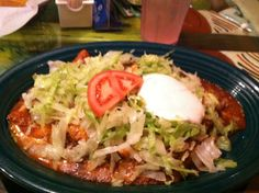 This is a mexican salad.with lettuce tomatoes and ham sour cream.