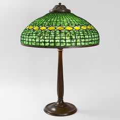 """Geometric Vine"" table lamp  A Tiffany Studios New York patinated bronze and leaded glass ""Geometric Vine"" table lamp. The shade features a band of yellow/green decoration against a geometric mottled green glass ground and sits atop a patinated bronze ""Stick"" base, circa 1900"