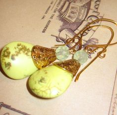 $16 These finely crafted magnesite earrings feature vibrant rich brass filigree bead caps. Hand hammered one of a kind brass hook hold the fantastic chartreuse magnesite briolette and a faceted chalcedony glass bead. The uplifting colors of this pair of earring are sure to brighten your day. Peking Chartreuse Droplets dangle 2.25 inches from the ear.    Peking Chartreuse Droplets will arrive to you on a decorative tag in an organza gift bag.