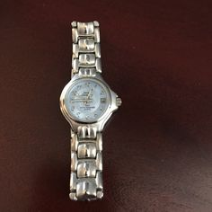 BRUSHED SILVER PLATE WOMENS WATCH This small faced woman's watch has a blue face with brushed silver plate. The designer is Sarah Coventry. It has the date window.**NEEDS BATTEY**Great condition no scratches on the face of the watch. Sarah Coventry Accessories Watches