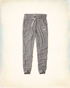 """Graphic Fleece Joggers Shown in Heather Grey Product Details This Absurdly Soft Fabric is our softest yet! Featuring a ribbed drawstring waist, side pockets, a logo graphic at left leg and ribbed cuffs, Imported Inseam: 28.5"""" Material and Care 75% Viscose, 21% Polyester, 4% Elastane Machine wash cold, with like colors Only non-chlorine bleach Lay flat to dry Low iron if needed Do not dry clean STORE ITEM: 352-521-0200-122 / WEB ITEM: 137011"""