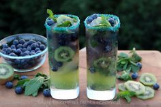 Kiwi Blueberry Mojito -  6 kiwis, peeled and cut in half or quartered 4 kiwis, peeled and sliced - to be used as garnishes 6 ounces of blueberries, to be crushed 6 ounce of blueberries, to be kept whole as garnishes ¼ cup fresh lime juice, from 1-2 limes ~ ½ cup sugar, adjust to taste 4 ounce pack of mint, leaves only 1 ½ - 2 cups of sparkling water 1 to 1 ½ cups of rum, adjust based on your preference Ice as needed Blue and/or green sugar to decorate glass rims