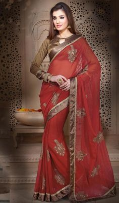 Look elegant in this maroon color shade chiffon net embroidered sari. The pretty resham work throughout the attire is awe-inspiring. Upon request we can make round front/back neck and short 6 inches sleeves regular saree blouse also. #ElegantLookRedEmbroideredSaree