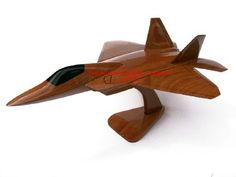 """A beautiful hand carved desktop model of the F-22 Raptor. The model has been carved from solid mahogany. The model comes boxed and is simple to assemble. The wings, tail fins and stand simply slot into pre-drilled holes on the body of the aircraft. No glue required.  Size H 8"""", L 11"""", W 9"""". Visit our website at http://www.thewoodenmodelcompany.co.uk to view the full range of our models."""