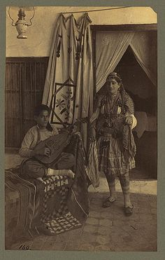 """""""Young man seated, playing an oud, while a young woman stands nearby, Tunisia"""" Dumas (1860-1900)"""