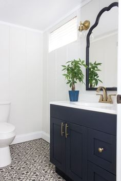 A basement bathroom update with a new faucet, light fixtures, hardware, and freshly painted vanity and walls. Vintage Modern style.