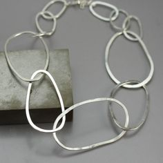 Modern, unique and bold, this sterling silver necklace is handcrafted from heavy gauge Argentium Sterling Silver wire. I made huge links out of the silver, shaped them into organic oval shapes and then hammered them flat to catch just the right amount of light. There are 5 large links in the front of the chain and then I went to a smaller link around the neck to prevent the piece from flipping around. The length is adjustable from 16-18 and because of the larger links, this fits more like a…