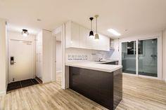 32평 아파트의 일자형 주방을 아일랜드 식탁 겸 조리대를 추가해서 실용적인 'ㄱ'주방으로 만들었습니다. 투톤의 식탁 등과 백색의 조각 타일 투톤의 싱크대의 조화가 심플한 구조입니다.