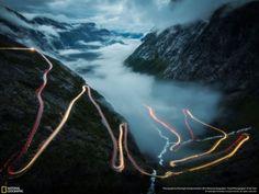 """Bø, More og Romsdal, Noruega. """"Tomé esta foto en julio de 2014 en Trollstigen en Noruega. Allí, de pie solo en la niebla, estaba esperando el tiro perfecto. Y entonces sucedió, la niebla desapareció y aunque era la una de la mañana, un coche se acercó lentamente por la carretera serpenteante. Siempre fue mi sueño tomar una foto de estelas de luz""""."""