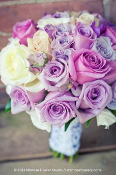 This bouquet featuring different shades of purple roses is so pretty for a spring wedding.