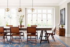 A dining space with a large dining table and chambray rug