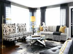 Chic modern living space with pops of yellow. Gray grasscloth wallpaper, Jonathan Adler Channing Buffet in White Lacquer, white  black cowhide rug, modern wingback chairs upholstered in Kelly Wearstler Bengal Bazaar Fabric in Graphite, oatmeal linen sofa with nailhead trim,