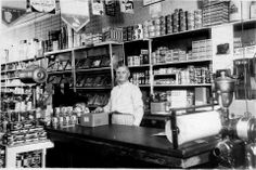 William E. Sweet stands behind the counter of his store. Sweet's Store was located on the SW corner of Dowling and Ferry St. in Montague, Michigan. The building still stands. Montague Michigan, White Lake, Grand Haven, Still Standing, Dry Goods, Retail Shop, Old Photos, Fence, Counter