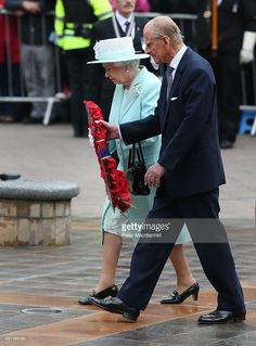 Queen Elizabeth II and Prince Philip, Duke of Edinburgh carry a wreath during a service at the war memorial on June 25, 2014 in Coleraine, Northern Ireland. The Royal party are visiting Northern Ireland for three days.
