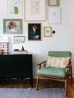 Modern eclectic gallery wall over a black console and mid-century modern chair - Art Wall Ideas