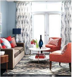 Be brave with your chairs.  Keep your furnishings, rugs and window treatments neutral, then add bright accent chairs.  A few more accessories in that same shade will pull the space together.