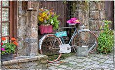 """Dinan. Panneau indicateur sur un vieux vélo posé devant la façade d'une belle maison bretonne. """"La mer à 3 km"""". Côtes d'Armor, Bretagne."""
