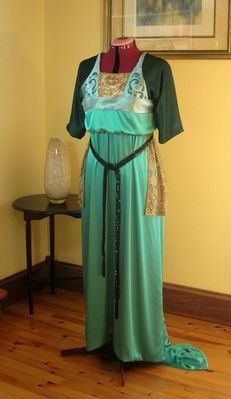 A 1913 replica from a French Edwardian evening gown design, in two colours of silk satin, silk chiffon, gold metallic lace, and original embroidery design (front view with mannequin slightly raised to display hem and train.