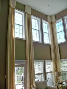 Elegant stationary panels custom designed for a great room with two story windows dresses the windows without blocking light.       By:  GG Design Inspirations