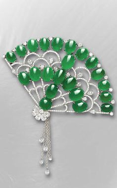 A JADEITE AND DIAMOND CLIP BROOCH/HAIR ORNAMENT  Set with twenty-two oval jadeite cabochon of bright emerald green colour and very good translucency, within a brilliant and pear-shaped diamond openwork fan, enhanced by a briolette diamond tassel, to the detachable hair ornament stem, mounted in 18k white gold, largest cabochons approximately 10.34 x 7.59 mm, fan 7.8 x 5.5 cm