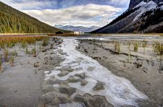 Frozen glacial run-off at far side of lake Louise with Chateau in blurry background