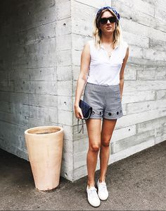 Camille Over The Rainbow wears a white tank top, plaid shorts with grommet detailing, and white sneakers