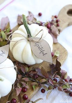 """Print several """"grateful, thankful, blessed"""" tags. Attach them to several little pumpkins using twine and put on a vintage cooking board to make a simple yet good looking Thanksgiving centerpiece."""