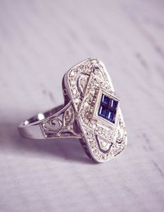 Stunning 1930s style, reproduction antique diamond and sapphire engagement ring. The Emma features 0.3 carats of sapphires, gorgeously surrounded by 0.5 carats of diamonds.