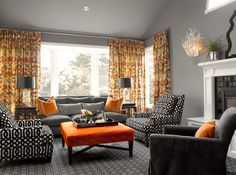 Gray and orange living room with gray walls and gray vaulted ceiling, orange and gray curtains, charcoal gray velvet sofa, white and black trellis chairs, square orange ottoman with French brass trim, orange velvet pillows with Greek key trim, ivory foo dog lamps with black vinyl lamp shades, charcoal gray rug, Jonathan Adler Queen Anne Mirror in Black and Moth Design Kiki Coral Sconce on fireplace.