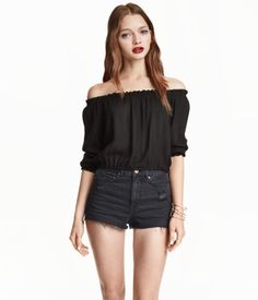 Black. Waist-length blouse in woven crêpe fabric with elastication at top, cuffs, and hem.