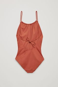 This swimsuit is designed with a strap that creates a gathered front, continues over the shoulders and ties at the back. Made from a smooth, stretchy fabric, it is completed with a soft, tonal lining.